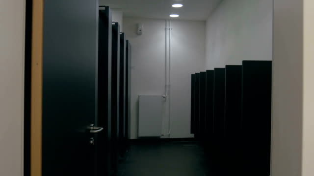 Into the Men's Public Bathroom Filming a men's public bathroom in Germany. The camera moves towards the wall and walks through to the end of the narrow interior. household fixture stock videos & royalty-free footage