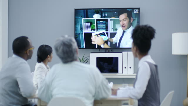 Introducing a new program to the team 4k footage of a group of businesspeople having a video conference online meeting stock videos & royalty-free footage