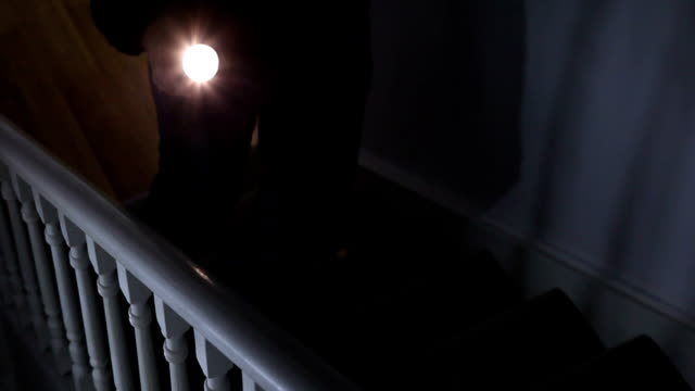 Intruder with flashlight on stairs. Looking down a dark staircase a male intruder with a flashlight or torch makes his way upstairs, with intent to burgle the property. It could also illustrate a power cut. flashlight stock videos & royalty-free footage