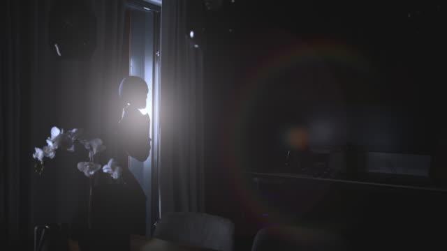 vídeos de stock e filmes b-roll de intrusion of a burglar holding a flashlight in an apartment at night - lanterna elétrica