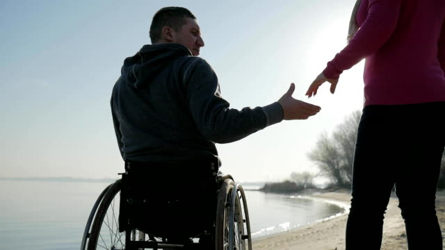 invalid love, handicapped gives hand to girlfriend, back view, cripple video