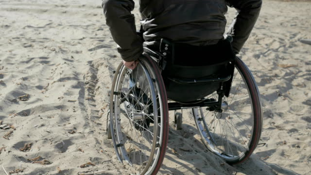 invalid person on wheel chair stuck in sand, Difficulties movement people with disabilities Disabled man in wheelchair video