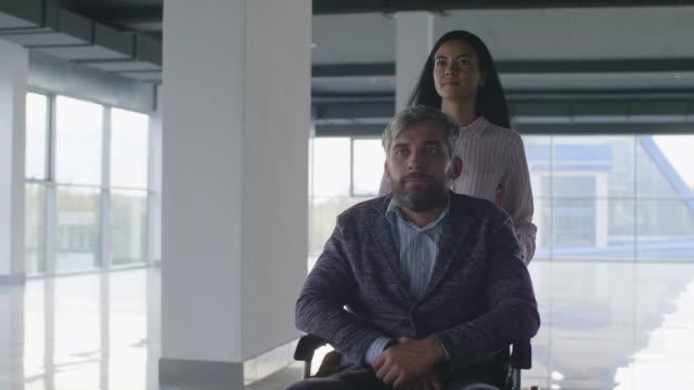 ogiltigt anbud hjälper patienten att flytta i rullstol - hospital studio bildbanksvideor och videomaterial från bakom kulisserna