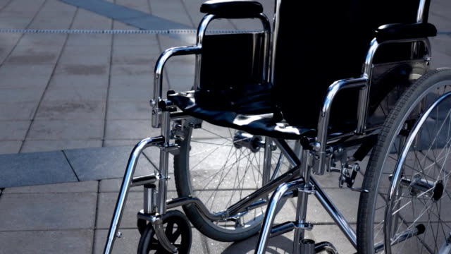 Invalid wheelchair rolling near modern building Invalid wheelchair rolling near modern building. Sunny teal and orange steadicam shot. Imminent illness concept. Disease. wheelchair stock videos & royalty-free footage