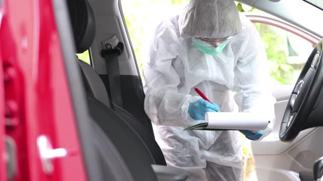 vídeos de stock, filmes e b-roll de investigador em traje de proteção tomando notas sobre a cena do crime - temas fotográficos