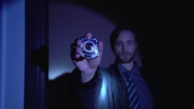 vídeos de stock, filmes e b-roll de investigador que mostra o emblema da polícia na câmera, prevenção do crime, aplicação de lei - distintivo