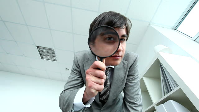 Investigator Curious man looking at something through magnifying glass magnifying glass stock videos & royalty-free footage