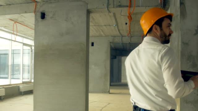 Investor inspecting building. Businessman in hard hat inside construction site examining construction progress video