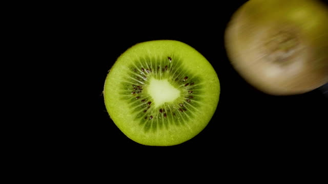 vídeos de stock e filmes b-roll de iolated green kiwi cut with a knife in the studio on a black background - kiwi