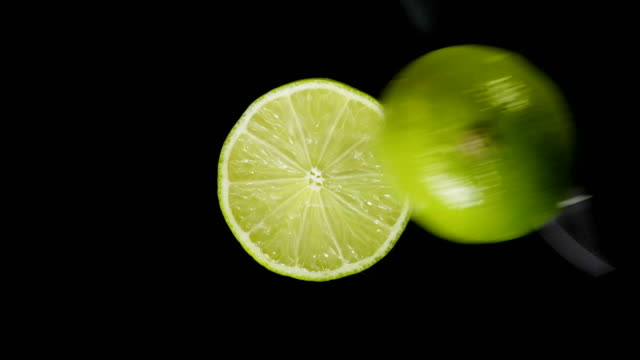 Iolated lime cut with a knife in the studio on a black background
