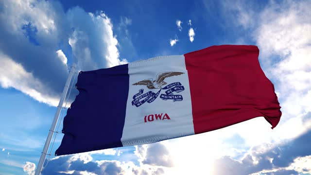 Iowa flag on a flagpole waving in the wind in the sky. State of Iowa in The United States of America