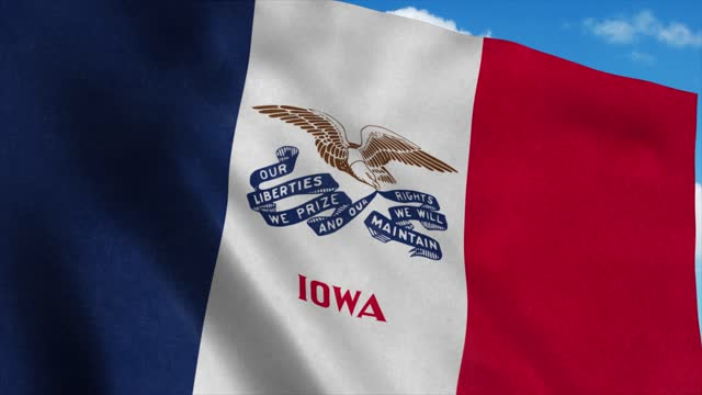 Iowa flag waving in the wind, blue sky background. 4K
