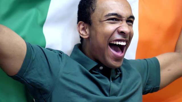 vídeos de stock e filmes b-roll de irish fan celebrating while holding the flag of ireland in slow motion - liga desportiva