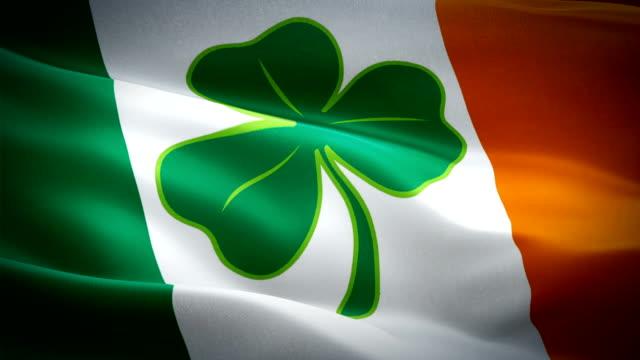 vídeos de stock, filmes e b-roll de bandeira irlandesa shamrock closeup 1080p full hd 1920x1080 filmagens de vídeo acenando ao vento com quatro folhas trevo. saint patrick dublin 3d bandeira irlandesa acenando. st pattys ireland animação de loop sem emenda. 4 folha trevo bandeira irlandes - boa sorte