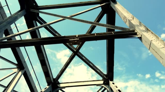 iron construction of bridge against blue sky with white clouds. driving under bridge, view of bridge from below. Silhouette of crossing steel beams. Bridge details against bright blue sky