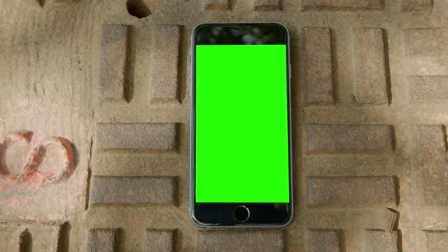 copertura in ferro smart phone schermo verde cromo riflesso sole - inquadratura fissa video stock e b–roll