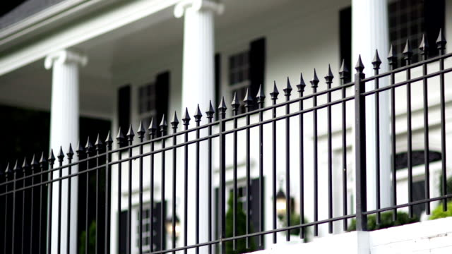 Iron Fence Iron rail fence with white brick columns and landscape plants. mansion stock videos & royalty-free footage