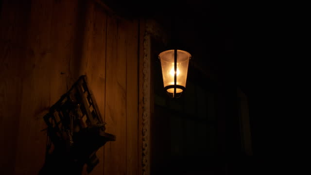 Iron lantern swaying in wind, night light, shadows on wooden wall of rustic barn. lonely lantern on dark street. Yellow light illuminates wall of building, wind sways it, shadows run along wooden wall, ominous atmosphere, warm light of lantern