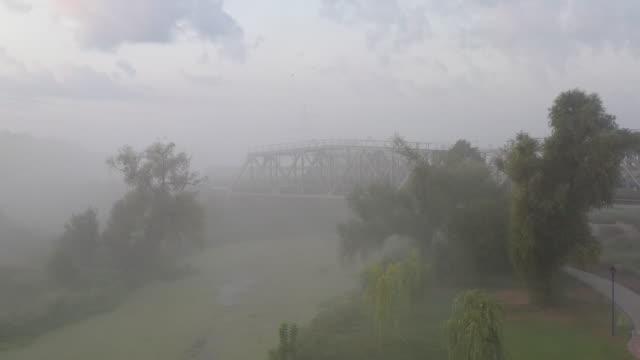 Iron railway bridge at dawn in the fog