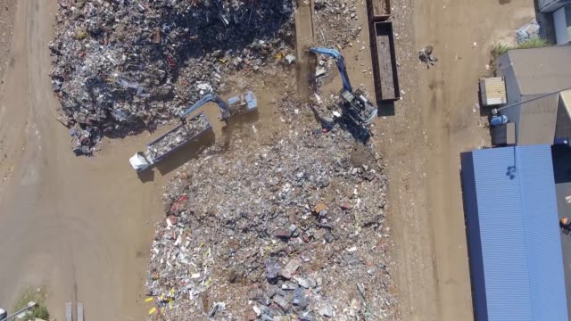 Iron raw materials recycling pile, work machines. Metal waste junkyard. Excavators diggers works on a garbage dump .View from above. video