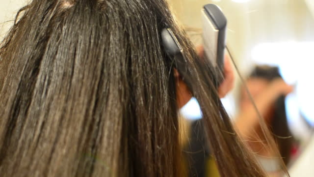 Ironing beautiful long hair of female model video