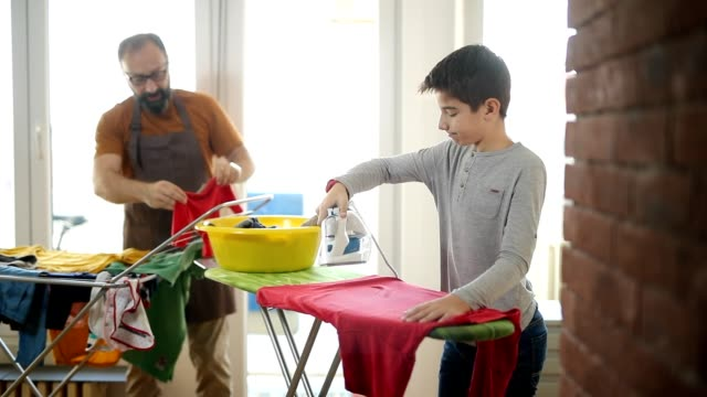 Ironing is fun Father and son ironing clothes together and having fun chores stock videos & royalty-free footage