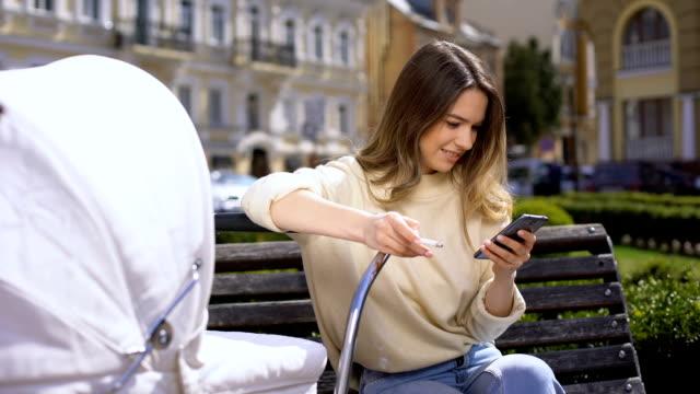 無責任な母親の喫煙とスマートフォンの写真を見て座って - ベンチ点の映像素材/bロール