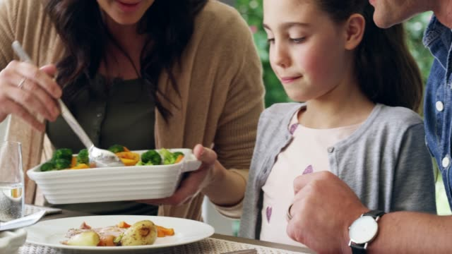 Is that enough for you? 4k video footage of an attractive woman dishing food for her daughter during a family lunch outdoors eating stock videos & royalty-free footage