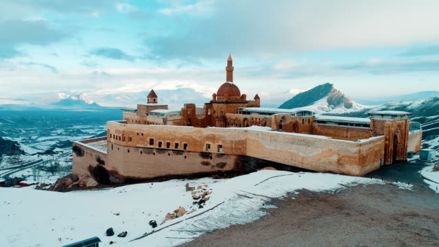 Ishak Pasha Palace - Snowy Mount Ararat - Drone Shot Aerial view of Ishak Pasha Palace (Turkish: İshak Paşa Sarayı) is a semi-ruined palace and administrative complex located in the Doğubeyazıt district of Ağrı province of eastern Turkey. The Ishak Pasha palace is an Ottoman-period palace whose construction was started in 1685 by Colak Abdi Pasha of the Cildirogullari, the bey of Beyazit province. Construction was continued by his son İshak Pasha and completed by his grandson Mehmet Pasha. According to the inscription on its door, the Harem Section of the palace was completed by his grandson Ishak (Isaac) Pasha in 1784. turkey stock videos & royalty-free footage