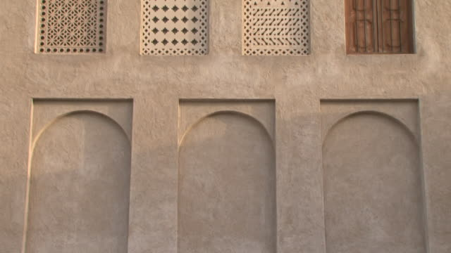 Islamic architecture Islamic architecture. Tilt-up from blind or false windows to the carved stone grills on the windows of a traditional house in Dubai. dubai architecture stock videos & royalty-free footage