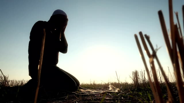 islamic man prostrating in the grass - ramadan stock videos and b-roll footage