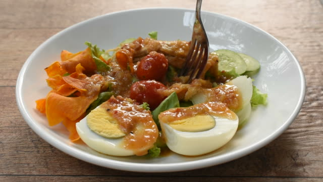 Islamic salad vegetable and boiled egg topping crispy fried taro dressing sweet bean sauce halal food stabbing by fork