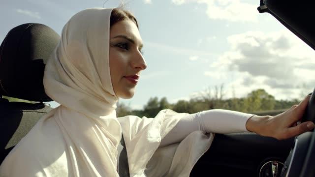 Islamic woman driving cabrio car