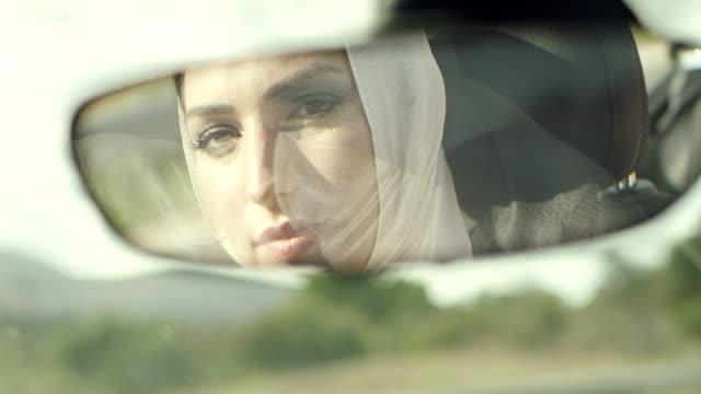 donna islamica alla guida di un'auto. all'interno ritratto dello specchio dell'auto - cultura del medio oriente video stock e b–roll