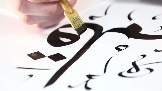 stockvideo's en b-roll-footage met islamitisch schrijven met de punt van een speciale pen - koran