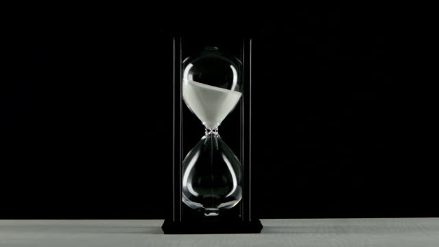 Isolated hourglass. Hourglass with white sand. Black White sand pours in a thin stream in the hourglass, hourglass with white sand, clock in wooden base, devastation of the bulb hourglass, on black background hourglass stock videos & royalty-free footage