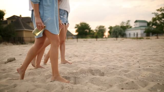 vídeos de stock e filmes b-roll de isolated view of three pairs of slim female legs with glass bottles of beverage in hands stepping on the beach by the sea at sunset in slow motion. young women drink beer walking on a sand. no face - amizade feminina
