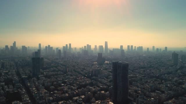 vídeos de stock, filmes e b-roll de israel horizonte de um drone amanhecer cedo. vista panorâmica aérea acima do litoral de tel aviv moderna e cidade de negócios com hotéis, litoral e praia. horizontes do oriente médio - sol nascente horizonte drone cidade