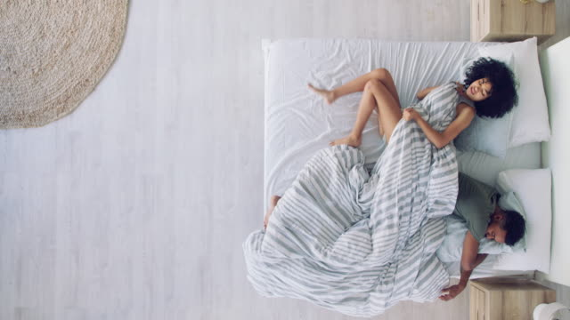 Issues with your marriage can cause issues with your sleep 4k video footage of a young couple fighting over the blankets in bed relationship breakup stock videos & royalty-free footage