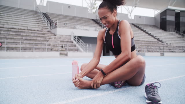 It happens to professionals and beginners! 4k video footage of a female athlete suffering from a sports injury while out on the track ankle stock videos & royalty-free footage