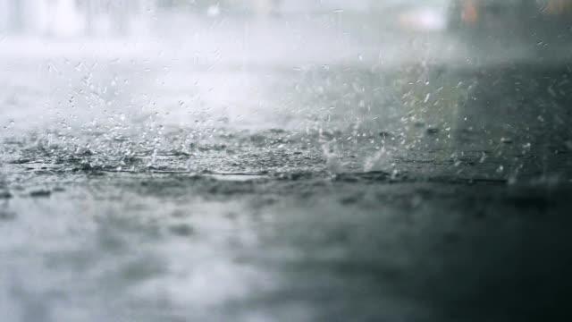 vídeos de stock e filmes b-roll de it is raining outside. rain drops break in a puddle. slow motion. 180fps - passagem de ano