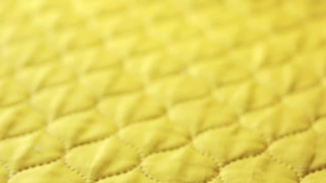 vídeos de stock e filmes b-roll de it is the yellow stitch quilt. background or texture. - edredão
