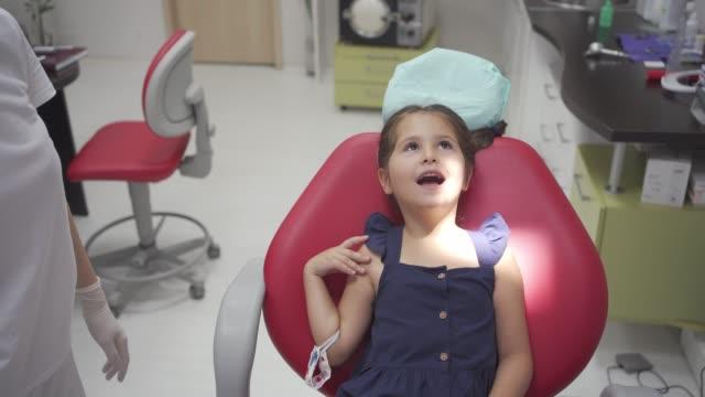 vídeos y material grabado en eventos de stock de es muy importante ayudar a su hijo a hacer un hábito de ir al dentista a chequear regularmente - ortodoncista