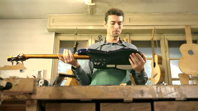 stockvideo's en b-roll-footage met italian adult man working as craftsman in guitar workshop - alleen één mid volwassen man