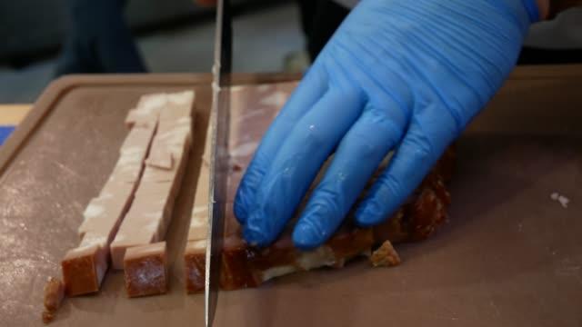 italian cooked sausage mortadella. chef cuts salami on small cubes. - mortadella video stock e b–roll
