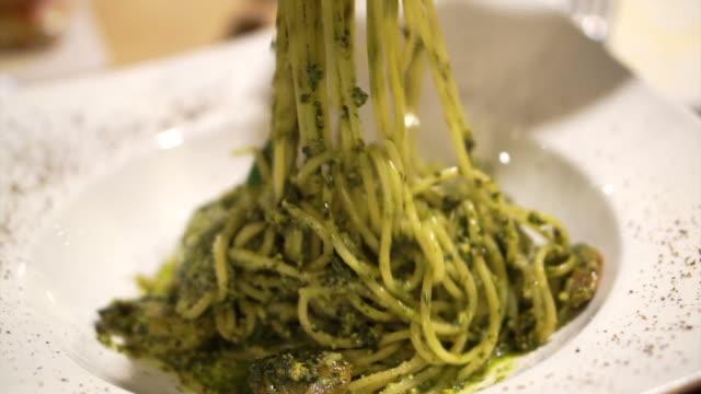 Italian pesto spaghetti. Hand using fork twirling, swirling to eat Italian pesto spaghetti. Hand using fork twirling, swirling to eat pesto sauce stock videos & royalty-free footage