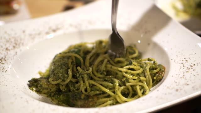 Italian pesto spaghetti. Hand using fork twirling, swirling to eat video