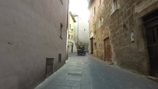 Italian Piaggio Ape tricycle driving in a narrow street in Umbria Italy