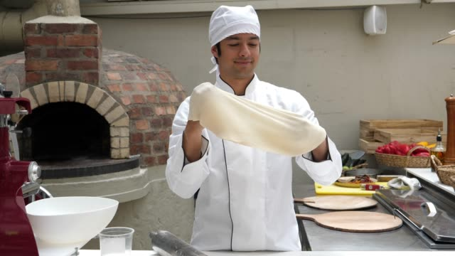 Italian sous chef at a restaurant making a pizza stretching the dough throwing it to the air smiling video