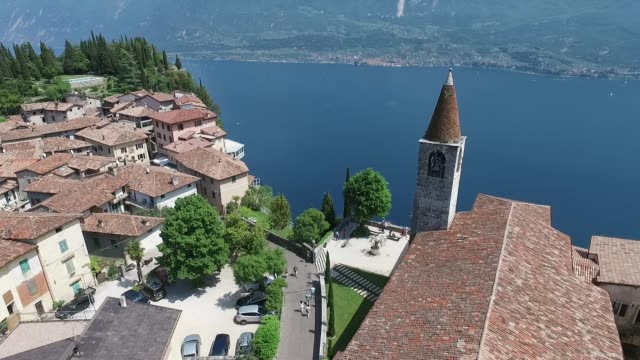 vídeos de stock e filmes b-roll de italy. church on the mountain and the old town. panorama of the gorgeous lake garda surrounded by mountains. video shooting with drone - margem do lago